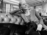 Lachende Frau mit einem Hund sitzt auf Sofa